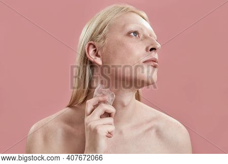 Young Caucasian Man With Long Blond Hair Using Quartz Massager On Neck While Standing On Pink Backgr