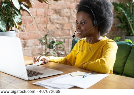 Focused Afro-american Employee Woman Wearing Headset, Communicating Via Video Call On Laptop, Talkin