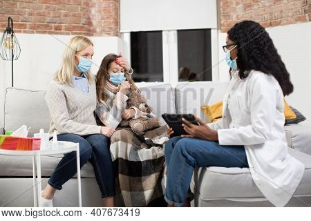 Doctors Visit At Home. Young Professional African American Female Doctor In Protective Mask, Visitin