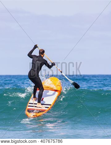 Vertical Image Man Caught The Wave. Surfing On Inflatable Sup Stand-up Paddle Board At Summer Sunny