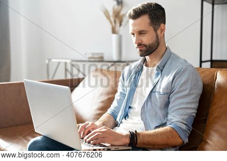 Clever Freelancer Using Laptop For Remote Work From Home. A Handsome Bearded Guy Websurfing, Sends A