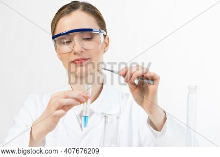 Young Female Research Scientist Puts Bio Sample Into Test Tube. Biochemistry Laboratory Analysis And