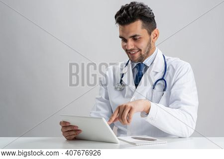 Young Smiling Internist Using Tablet Computer. Serious Therapist In White Medical Gown With Stethosc