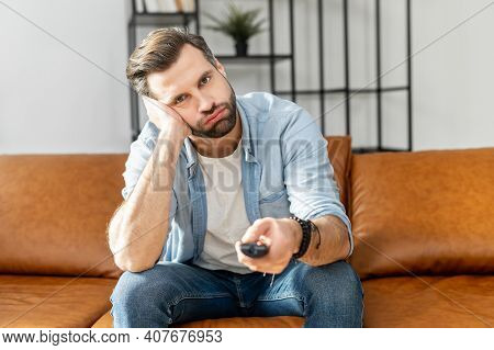 Handsome Bored Young Man Holding Tv Remote Control, Watching Boring Tv Shows, Switch Channels