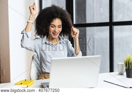 Excited Lucky Mixed-race Businesswoman Raised Fists Up Celebrating Success, Making Yes Gesture, Look