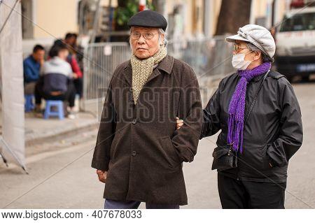Hanoi, Vietnam - January 13, 2018. A Local Elderly Couple Walk Along The Street In The Center Of Han