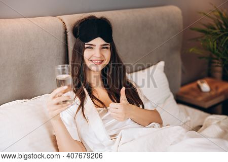 Young Woman Shows That Drinking Water Is In The Bed. Model With Brown Hair With A Glass Of Water In