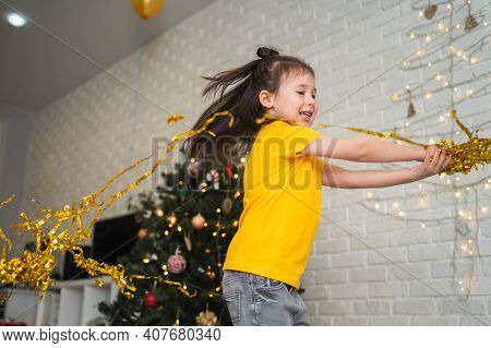 A Joyful Child Catches Tinsel. A Bright Children's Holiday. A Child In A Yellow T-shirt Catches A Se