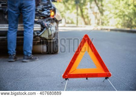 Red Emergency Stop Triangle Sign Afore Destroyed Car In Car Crash Traffic Accident On City Road. Man