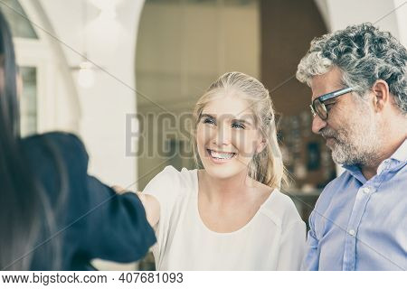 Happy Adult Daughter And Mature Father Meeting With Family Consultant At Co-working, Shaking Hands.
