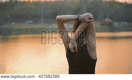 A Young Woman Is Warming Up Before Running In Nature Outdoor At Sunset .