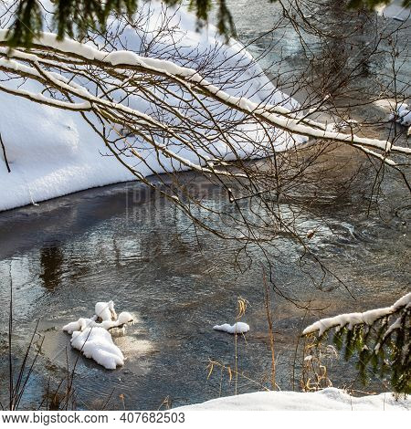 Flowing River In A Snowy Winter Forest. Tree Branches Covered With Fresh Snow During Winter Christma
