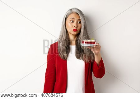 Elegant Senior Woman In Red Blazer Wants Take Bite Of Sweet Cake, Looking With Tempted Face At Desse