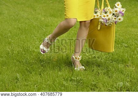 Walking Young Woman In Sandals With Daisies On Her Feet And Flowers In A Yellow Bag.