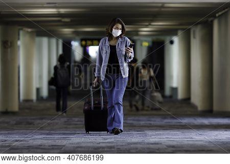 Beautiful Asian Traveler Wearing Hygiene Protective Mask Holding Luggage Bag Walking And Using Smart