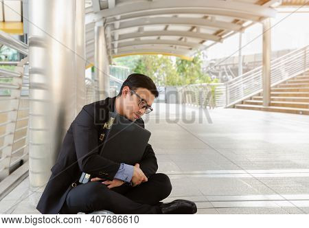 Fired Businessman In Suit Holding Briefcase And Sitting On Floor In City Outdoors. Unemployed Man De