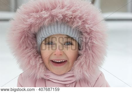 Portrait Of A Laughing Little Girl In Winter Clothes In The Snow In Winter Close-up, Childrens Emoti