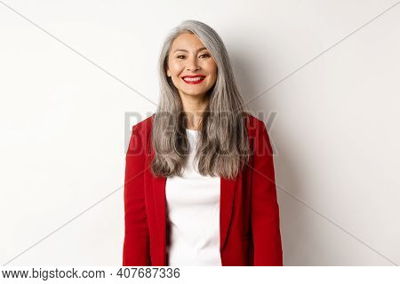 Business People. Senior Smiling Asian Woman With Red Lipstick And Blazer Looking Happy, Standing Ove