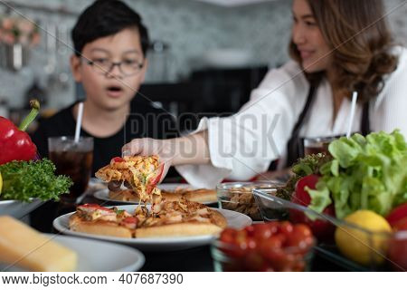 Asian Mom And Son Sitting In Home Kitchen And Eating Homemade Pizza Together With Various Kinds Of V