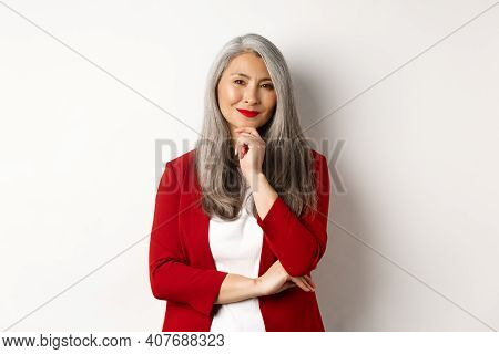 Business Concept. Asian Mature Businesswoman Smiling Pleased, Looking Thoughtful, Having An Idea, St