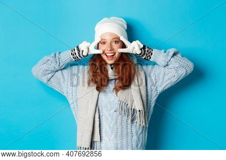 Winter And Holidays Concept. Cute Redhead Teen Girl In Beania, Gloves And Sweater Showing Peace Sign