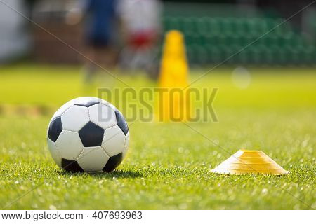 Soccer Ball And Yellow Cone Marker On Training Pitch. Football Turf. Soccer Stadium In Blurred Backg