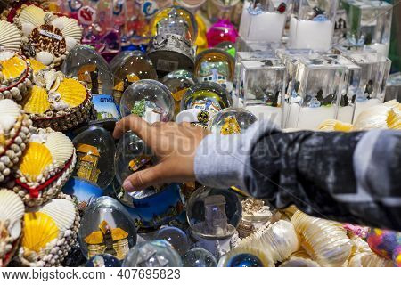 Child's Hand Grabbing Snowglobe Tourist Souvenir From Market Stand With Souvenirs From Gdansk And So