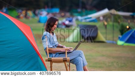 Female Traveler Sitting Beside Camping Tent And Using Notebook Laptop Computer Working With Other Te