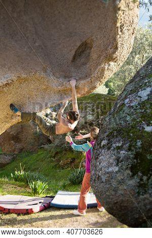 Sport Climbing. An Athlete Climbs A Difficult Track On A Rock. Rock Climber Climbing A Boulder In Th