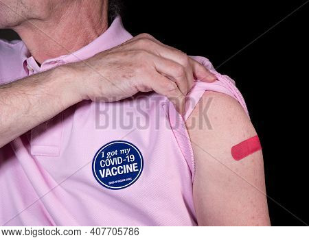 Senior Adult Man Showing His Adhesive Plaster Over His Covid-19 Vaccination With Sticker Saying He G