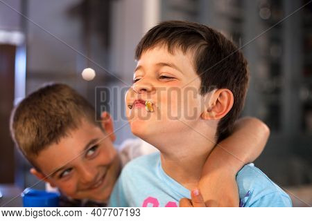 Caucasian Boy With Mouth Full Of Food Laughing With His Brother. Hungry Child Eating Big Chocolate P