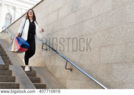 Tourist Girl Walks Around City And Makes Purchases. Woman Walking Down Stairs And Holding Purchases.
