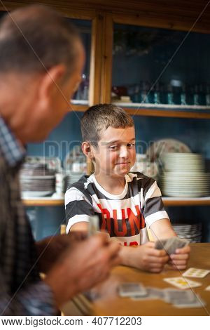 8 Years-old Boy Sitting Around A Table, Playing Cards With His Family. Kid With Pouting Face Looking