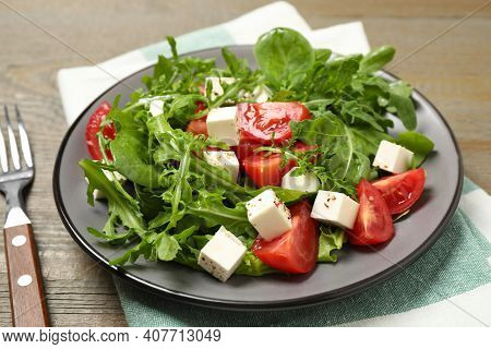 Delicious Salad With Feta Cheese, Arugula And Tomatoes On Wooden Table, Closeup