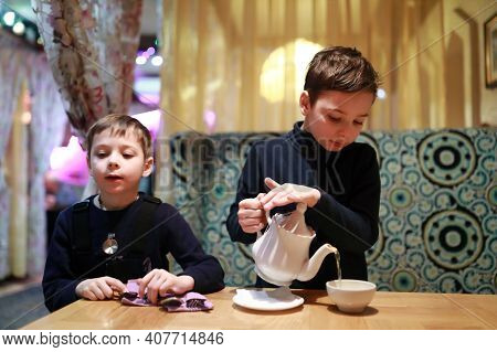 Portrait Of Child Pouring Tea In Restaurant