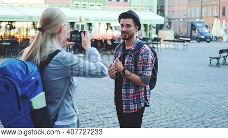 Couple Of Tourists Making Photos With Photo Camera On Historical Market Square. Man Posing And Woman