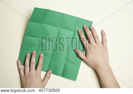 Young Hands And A Square Of Green Paper With Marked Folds, To Make An Origami Figure. Concepts: Orig