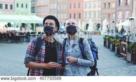 Man And Woman Tourists In Protective Masks And With Bags Using Smartphone. They Looking For Interest