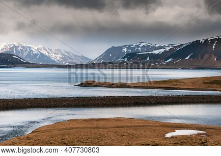 Icelandic Dramatic Landscape With Frozen Lake And Mountains Covered In Snow At Snaefellsnes Peninsul