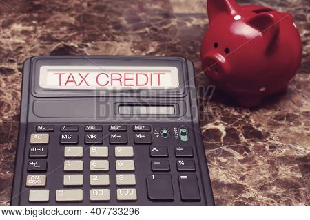 Tax Credit. The Text On The Screen Of The Calculator Lying Next To The Piggy Bank On The Table. Clai