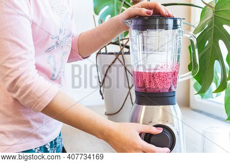 A Woman Mixes Berry Smoothie In A Blender. The Concept Of A Healthy Lifestyle.