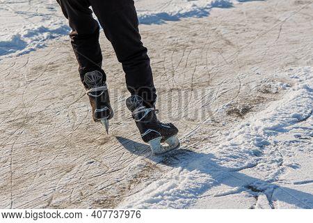 Skater Legs At Skating Rink. Man Skating On White Ice On Frozen Lake. Rear View. Winter Leisure Acti