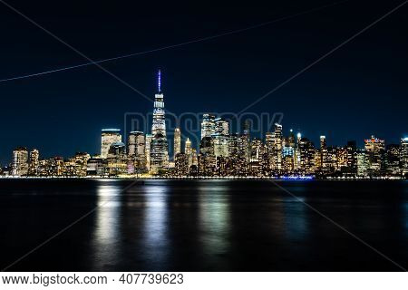 New York City Skyline At Night With Reflection Of The Skyline In The Hudson River