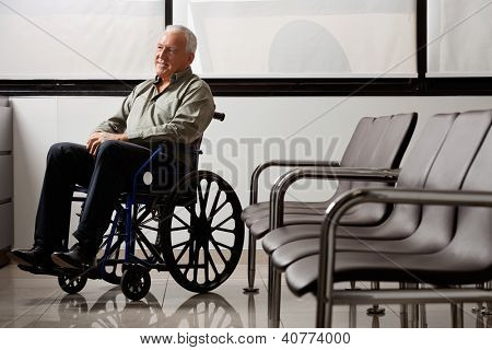 Full length of senior man on wheelchair looking away while waiting in hospital lobby