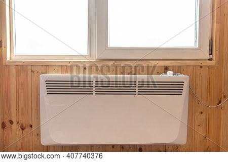Electric Radiator Under The Window Of A Country House Whose Walls Are Finished With Clapboard