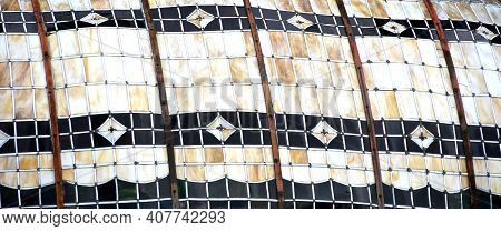 Old Stained Glass Canopy Has Metal Bands Holding It Together.  Black With White And Tan Coloring.