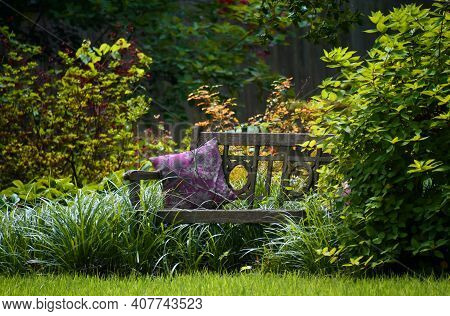 Rough, Wooden Bench Sits Forgotten In Backyard Garden.  Decorative Pillow Shares Bench With Bare Bra