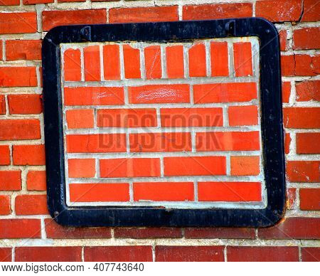 Background Image Is An Old Brick Wall.  Black Metal Frame Is Mounted On Wall.