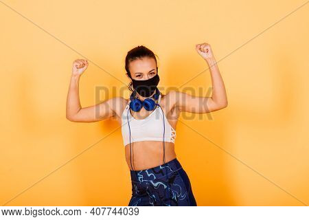 Portrait Of Fit African Woman Wearing Face Mask. Sporty Woman In Fitness Wear Standing On Yellow Bac