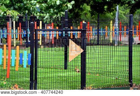 Fenced In Grass Area Is A Memphis, Tennessee Dog Park.  It Is Decorated With Colorful Metal Strips A